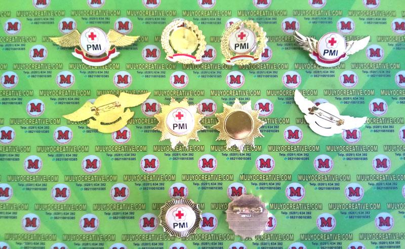 Pin PMI dalam berbagai model, dengan bahan logam kuningan, dan logo pmi yang sudah di resin